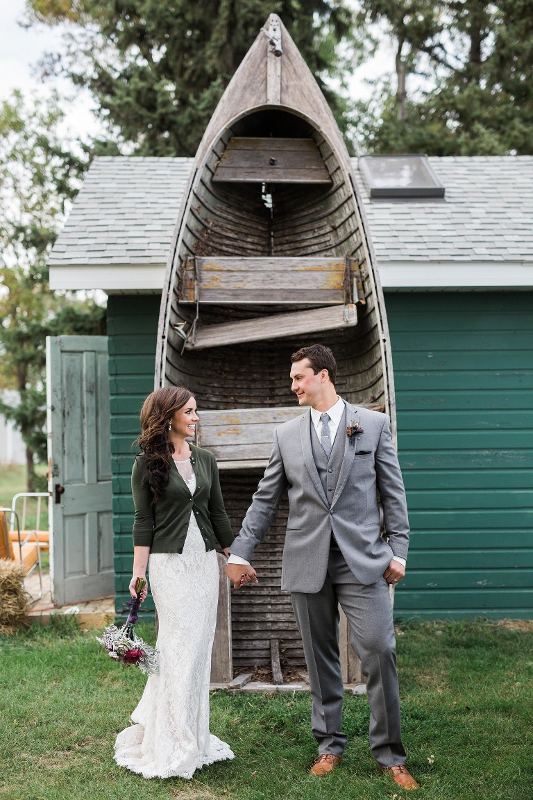 bride and groom in front of old wooden boat fall wedding