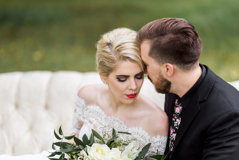 classic bride with red lipstick sitting on vintage white couch with hipster groom