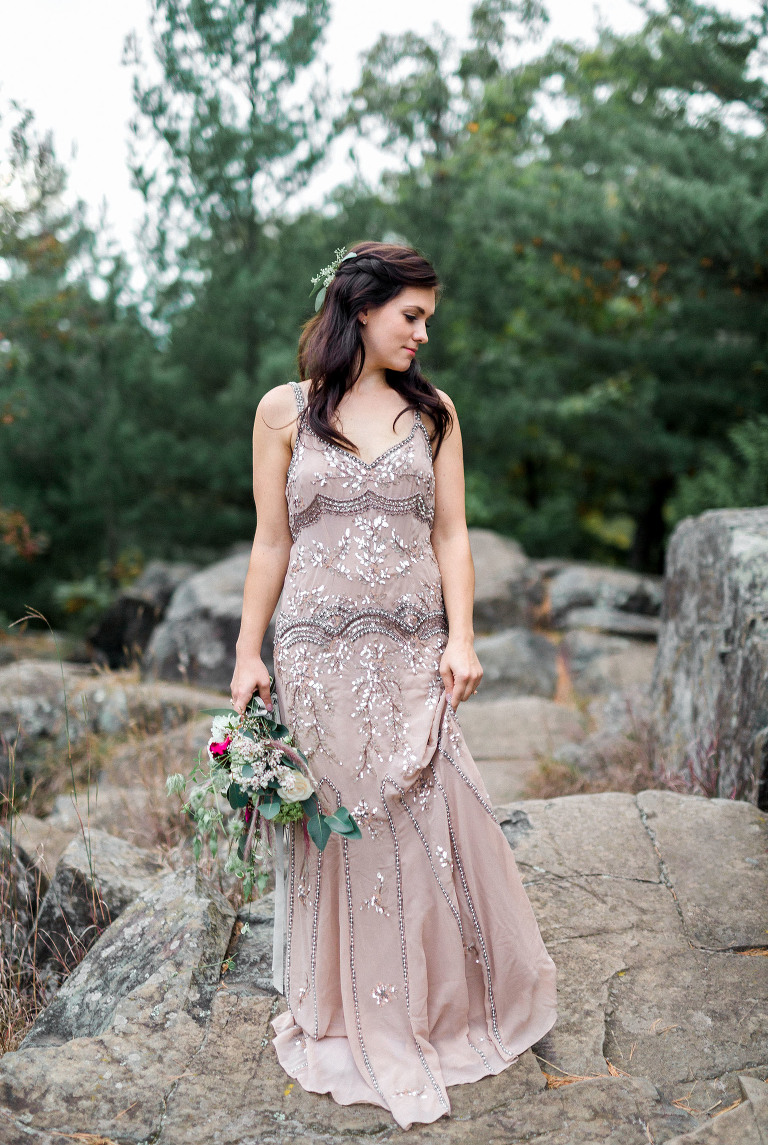 bride holding hem of vintage beaded gown standing on cliff