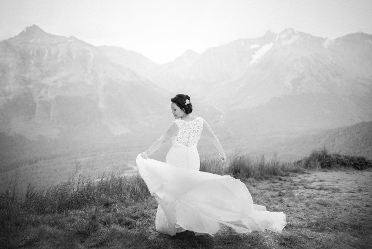 bride spinning her dress in the wind on an alaskan mountain
