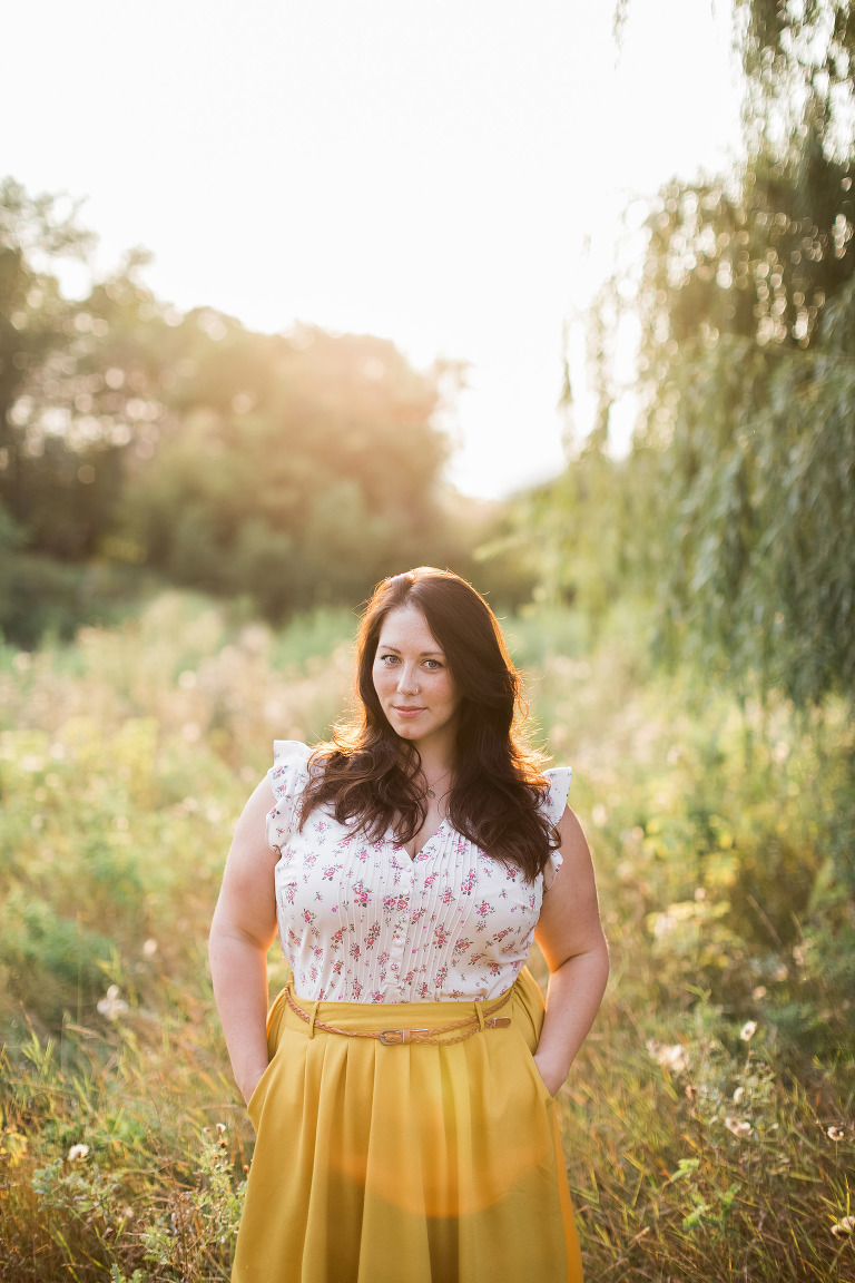 golden hour portrait of photographer in yellow skirt in front of a willow tree